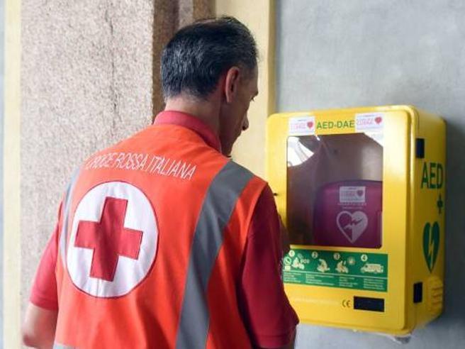 operatore della croce rossa che guarda un defibrillatore