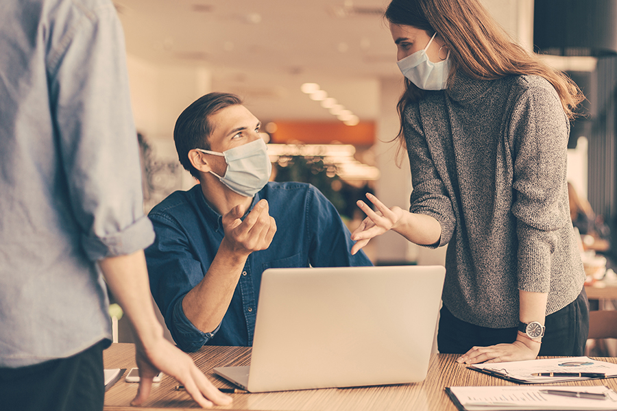 Persone con mascherina chirurgica che parlano davanti al PC